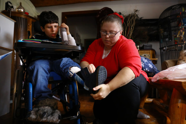 Bobbie Kasper, a personal care worker, puts a foot brace on Adrian Strauss at his home in Jefferson, Wis., on Nov. 15, 2017. Home health care providers and family planning clinics have sued the state of Wisconsin, alleging they have been ordered to repay money for services that were provided but which the state claims were not properly documented. Photo by Coburn Dukehart / Wisconsin Center for Investigative Journalism.