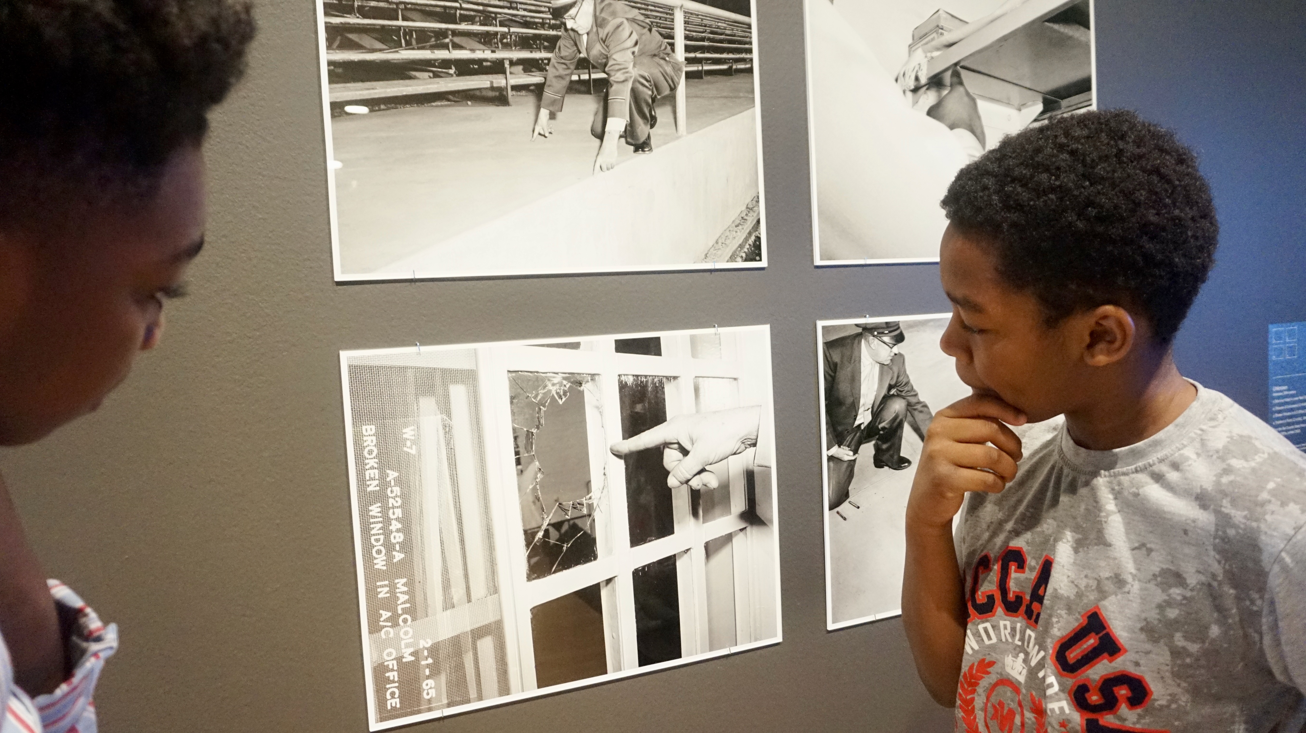 Lorenz Ambose, 12, (left) and Carmello Mitchell, 10, study a photo in the exhibit. Photo courtesy of NNS.