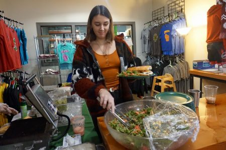 Paris Breen, a junior at Escuela Verde, serves salad to customers at Sabor Verde. Photo by Sarah Lipo/NNS.