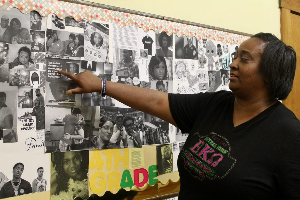 Monica Kendrick points to collages made by her fourth-grade students in memory of Sandra Parks. Photo by Allison Dikanovic/NNS.