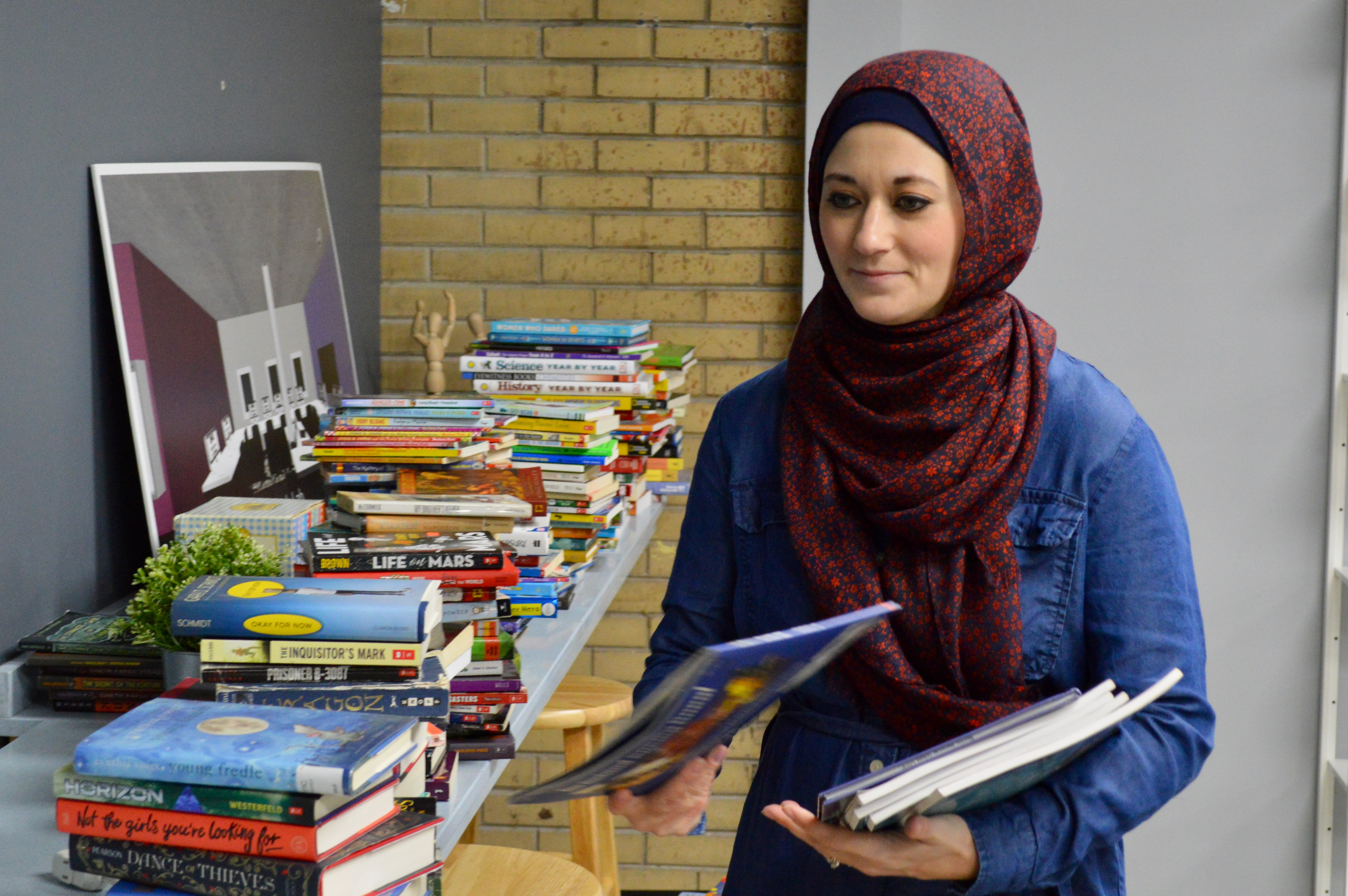 Brittany Khatib, a Ma'ruf volunteer, sorts books in the center's library. Photo by Ana Martinez-Ortiz/NNS.