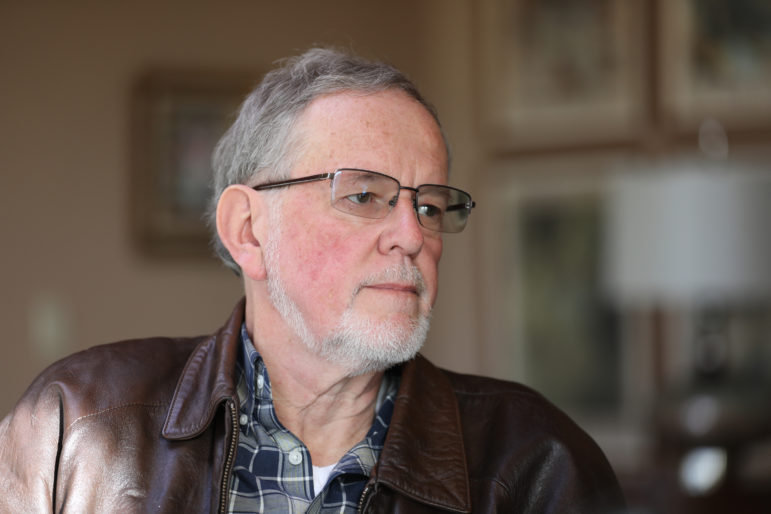 Richard Jinkins sits in the living room of Alan Jewell near Dodgeville, Wis., on Dec. 18, 2018. Jinkins has family land next to a proposed solar farm. Jinkins says his family purchased its farmland before Wisconsin became a state in 1848, and his son hopes to become a fifth-generation farmer. But he says the large-scale solar farm is a threat to Wisconsin's farming legacy. Photo by Emily Hamer / Wisconsin Center for Investigative Journalism.