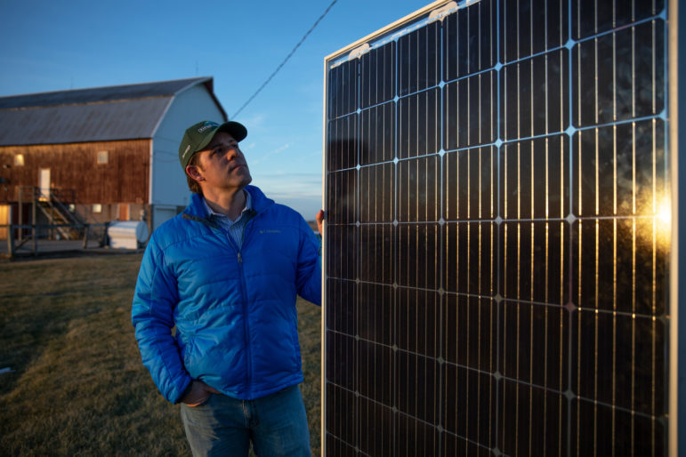 Invenergy's renewable energy manager, Dan Litchfield, shows a single solar panel outside of the company's office in Cobb, Wis., on Dec. 18, 2018. These panels would become part of a 3,500-acre solar project, one of the largest solar farms on cropland in the nation. Photo by Emily Hamer / Wisconsin Center for Investigative Journalism.