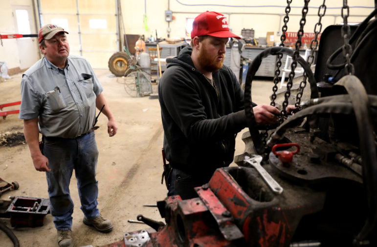 Bob Bishop, left, works with his son Andrew Bishop to remove the center section of a transmission on a tractor at their farm in Cobb, Wis., on Jan. 18, 2019. The Bishops plan to rent 650 acres of their farmland to Invenergy, a company proposing to build a giant solar power project in the area. Invenergy's Badger Hollow Solar Farm would be the largest such project in the Midwest. Photo by Coburn Dukehart / Wisconsin Center for Investigative Journalism.