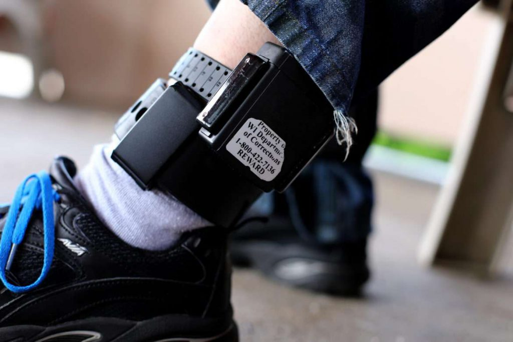 A registered sex offender shows his GPS ankle bracelet. Many such offenders on electronic monitoring become homeless because of restrictive housing laws that prohibit them from living near schools, parks and day-care centers. Photo by Coburn Dukehart/Wisconsin Center for Investigative Journalism.