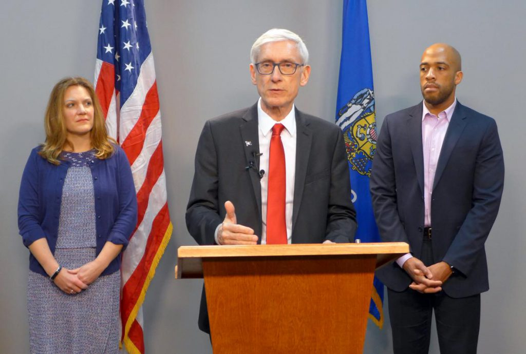 Gov. Tony Evers, joined by DHS Secretary Andrea Palm, left, and Lt. Gov. Mandela Barnes, speaks in La Crosse, Wis. on Tuesday, Jan. 8, 2019. Photo by Hope Kirwan/WPR.