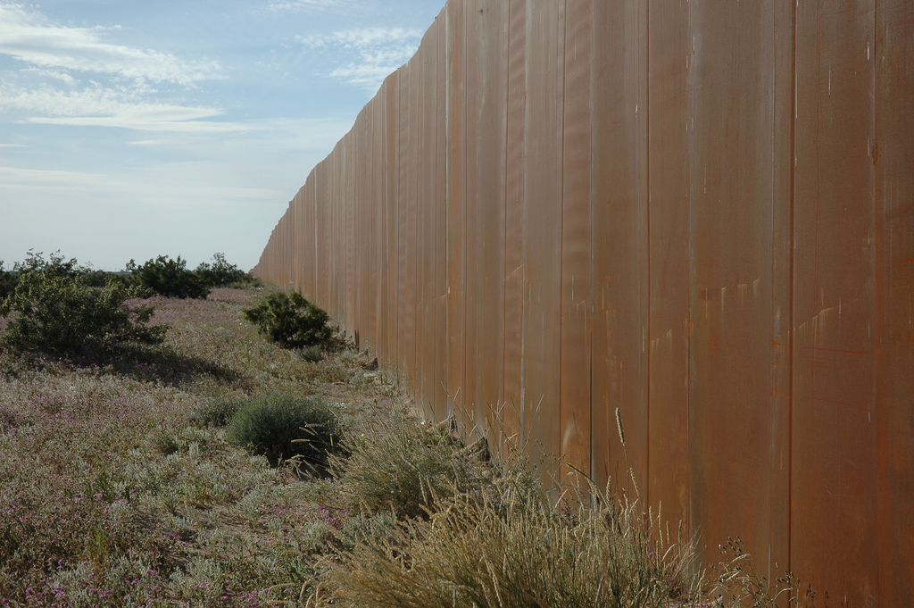 A wall seperating the US and Mexico. Photo by Wonderlane. (CC BY 2.0)