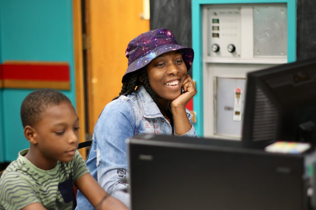 Syier Kern works in the computer lab at City on a Hill, while his mother, Rebecca Ford, looks on. Kern participated in the Bridge Milwaukee pilot program. Photo courtesy of Digital Bridge/NNS.