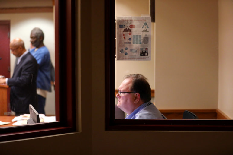 A flyer explaining the Public Safety Assessment is pasted to a window at initial appearance court at the Dane County Public Safety Building on May 25, 2018. Dane County is piloting the PSA, an algorithm that predicts the risk of a defendant committing a new crime or skipping out on court. Pictured in the window is Clark Rodgers, who prepares the PSA reports. Photo by Coburn Dukehart/Wisconsin Center for Investigative Journalism.