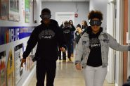 "Two students attempt to walk down the hallway wearing ""impairment goggles"" that blurred their vision in a way that a person impaired by drugs would experience. Photo by Analise Pruni/NNS."