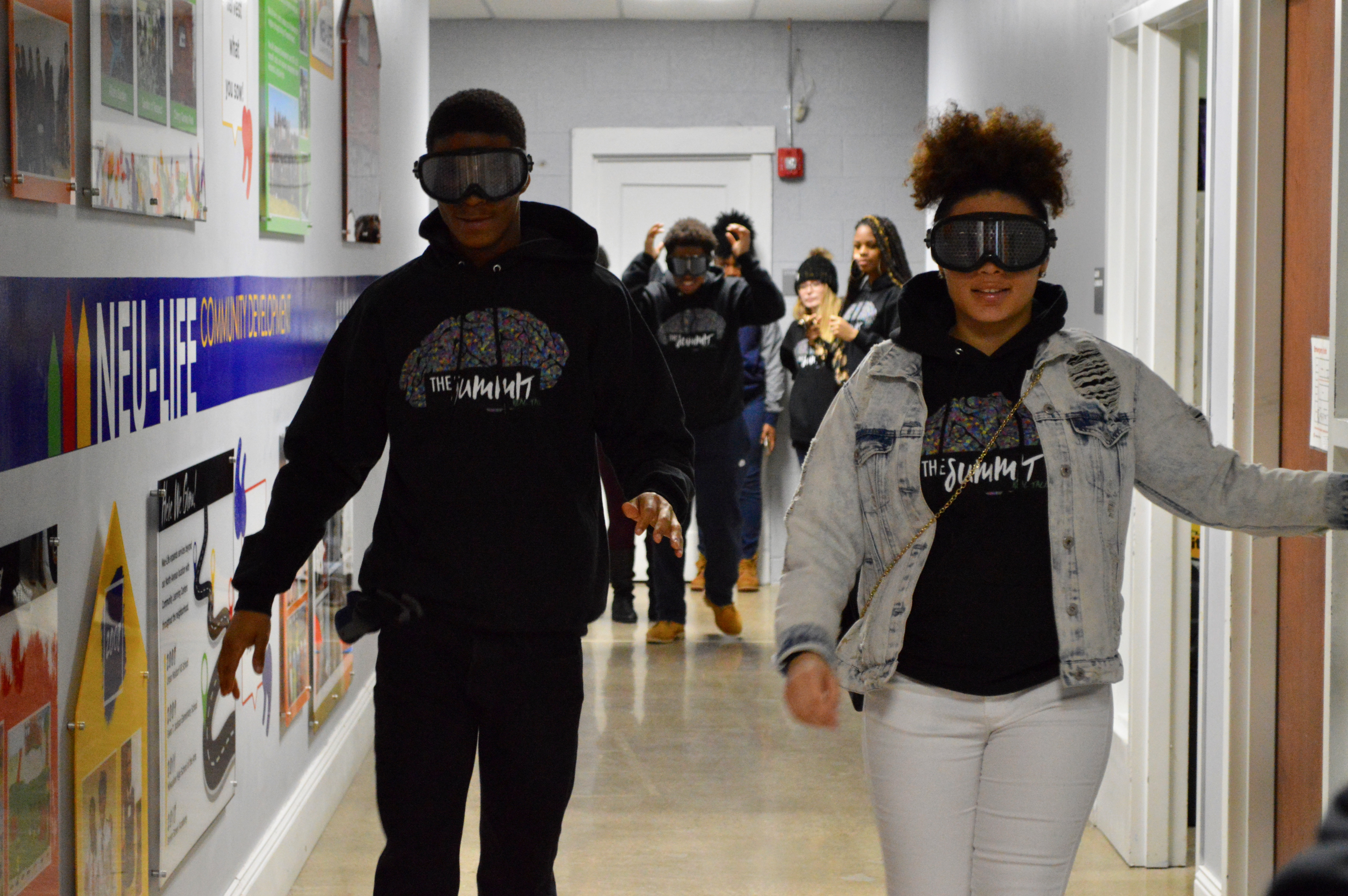 """Two students attempt to walk down the hallway wearing """"impairment goggles"""" that blurred their vision in a way that a person impaired by drugs would experience. Photo by Analise Pruni/NNS."""