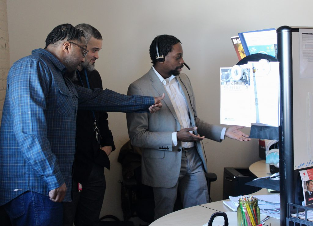 William Cainion (left) gives a thumbs up to a man inside prison who just earned his GED through a video conference. (Photo by Allison Dikanovic)