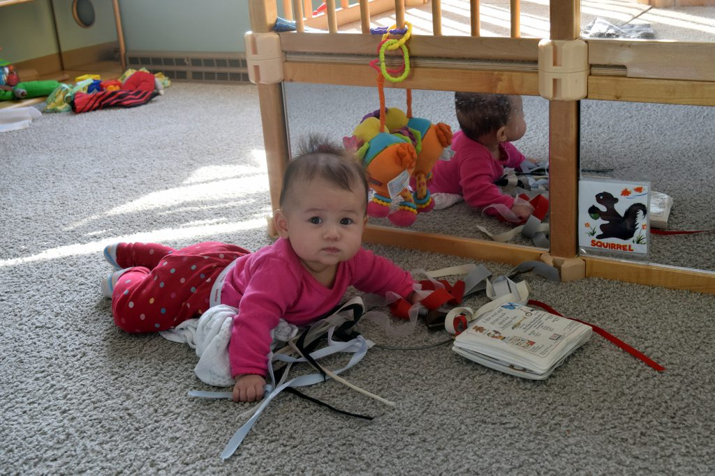 Maya Hamilton, 5 months, spends her days in the infant room at Saint Mary's Hospital Child Care Center, with seven other infants and two primary teachers. Her older brother Chase Hamilton also attends the child care center. Photo by Phoebe Petrovic/WPR.
