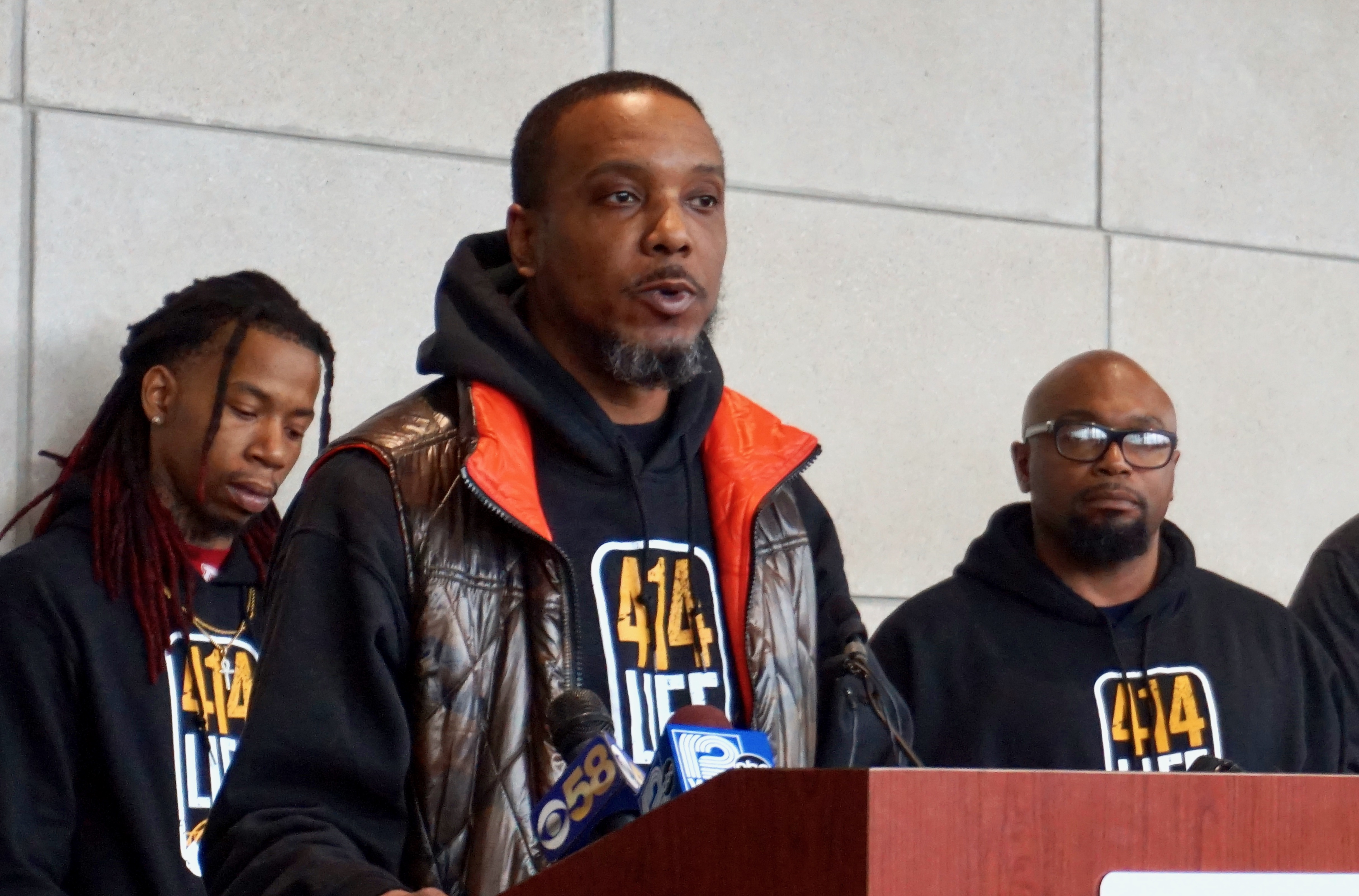 """Chris Conley, 414 Life outreach and resource coordinator, Uniting Garden Homes, standing with the """"interrupters"""" team, speaks to the press at the Froedtert Cancer Center. Photo by Andrea Waxman/NNS."""
