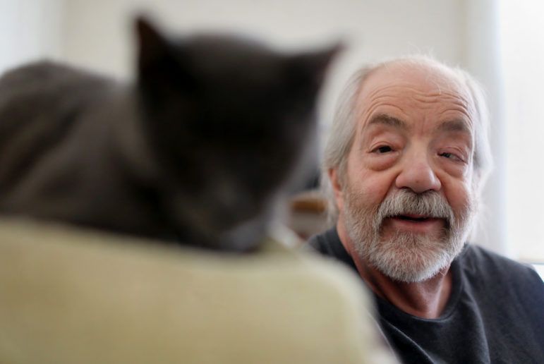 Madison, Wis., resident Gary Storck has suffered from glaucoma since he was a child. When he was a teenager, Storck read that marijuana could relieve the pressure and pain in his eyes, and he has been using it as a medicine ever since. He is seen in his apartment in Madison with his cat, Roy, on March 20. Photo by Coburn Dukehart/Wisconsin Center for Investigative Journalism.