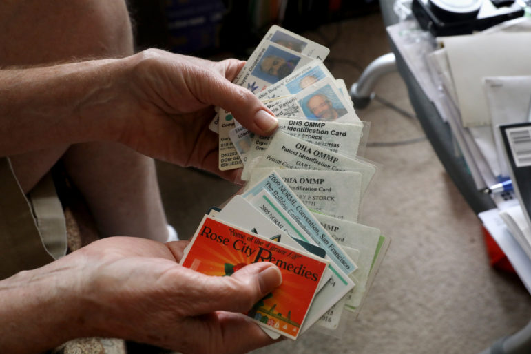 Madison, Wis., resident Gary Storck shows out-of-state medical marijuana cards and marijuana-related memorabilia. Storck uses the cards under an obscure Wisconsin law that allows patients to have a controlled substance with a valid prescription or order from a doctor. Storck uses cannabis to relieve the symptoms of glaucoma. Photo by Coburn Dukehart/Wisconsin Center for Investigative Journalism.