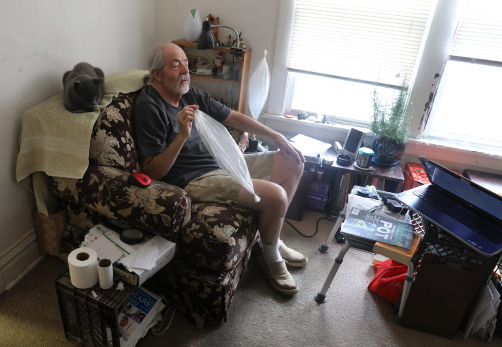 "Madison, Wis., resident Gary Storck inhales marijuana from a vaporizer in his apartment on March 20. Storck favors Gov. Tony Evers' proposals to legalize cannabis for medical use and to decriminalize possession of small amounts of the drug. Says Storck: ""These issues have majority popular support."" Photo by Coburn Dukehart/Wisconsin Center for Investigative Journalism."