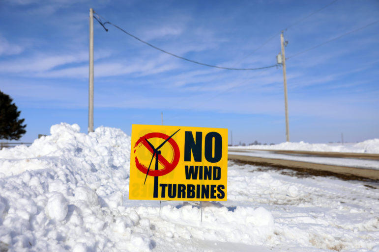 "A sign that reads ""No Wind Turbines"" sits in Jim Bauman's front yard in Juda, Wis. Jim says his brother, Brian Bauman, has signed a contract with EDF Renewables to install a wind turbine and a power station on his property — directly across the road from Jim's. ""We are an agricultural community. We like our landscapes the way they are. This will make us an industrial community,"" he says. Photo by Coburn Dukehart / Wisconsin Center for Investigative Journalism."