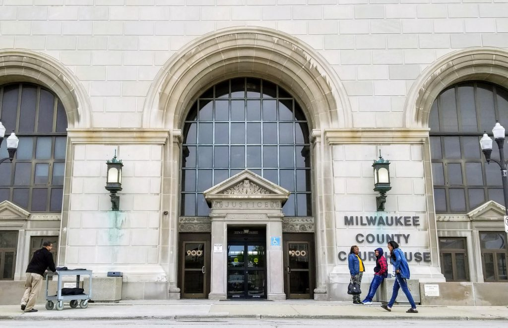 In this Tuesday, May 21, 2019 photo, people stand outside the Milwaukee County Courthouse in downtown Milwaukee. Photo by Kyla Calvert Mason/WPR.