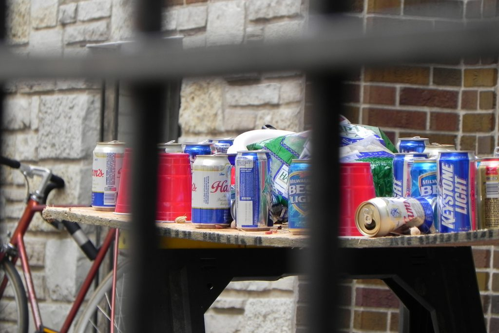 Empty beer cans cover a makeshift table in Madison on a football Saturday in 2010. Photo by Richard Hurd (CC BY 2.0)
