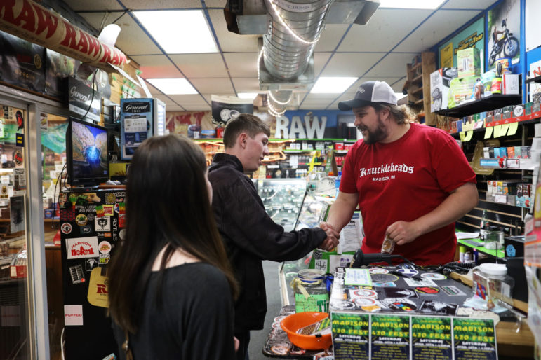 General manager Landon Meske helps Justin Feldbruegge purchase a glass water pipe at Knuckleheads, a CBD and vape shop in Madison, Wis., on April 15, 2019. Also pictured is Chelsey Krueger, who helped Feldbruegge pick out the pipe. Meske says he favors marijuana legalization for medical and recreational uses. Photo by Emily Hamer / Wisconsin Center for Investigative Journalism.