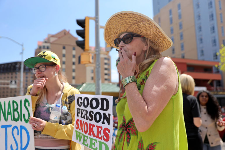 "Liisa Kemp, 60, smokes a joint as supporters gather for a pro-marijuana legalization march in Madison, Wis., on May 4, 2019. ""I've been smoking pot since 1976,"" Kemp says, adding that she has always worked full-time, has traveled the country and owns a house. At left, Caysie Dolan, 22, says she smokes marijuana to help with her post-traumatic stress disorder from a 2012 car accident. She says she has tried 13 different pharmaceuticals and none has worked as well as marijuana. Photo by Emily Hamer / Wisconsin Center for Investigative Journalism."