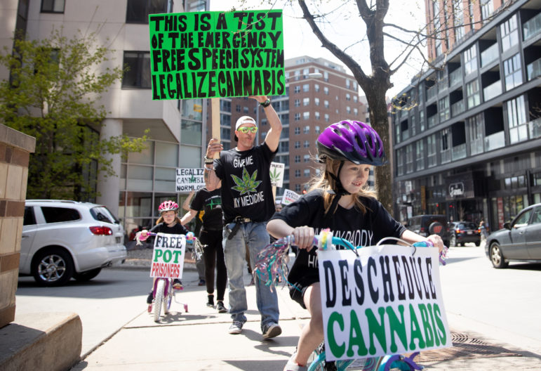 "Kendall Seamonson, 6, participates in a pro-marijuana legalization march in Madison, Wis., on May 4, 2019. Kendall's shirt reads, ""Give my daddy his medicine."" Her father, Brian Seamonson, is deputy director of Madison NORML, a pro-legalization group. Photo by Emily Hamer / Wisconsin Center for Investigative Journalism."