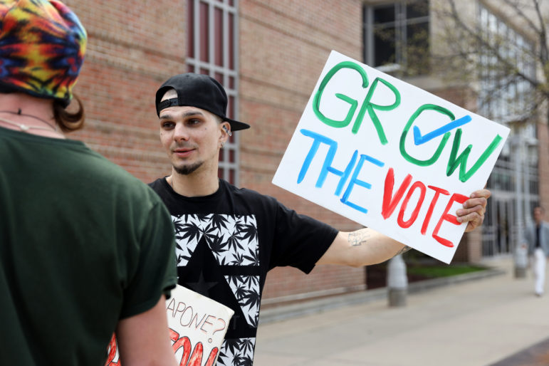 "Matthew Gethard, 30, of Milwaukee holds a sign reading ""Grow the Vote"" in downtown Madison, Wis., after a march for legalizing marijuana on May 4, 2019. The event was organized by Madison NORML, an organization that works to legalize marijuana, and Quality CBD, a health and beauty shop in Madison. Photo by Emily Hamer / Wisconsin Center for Investigative Journalism."
