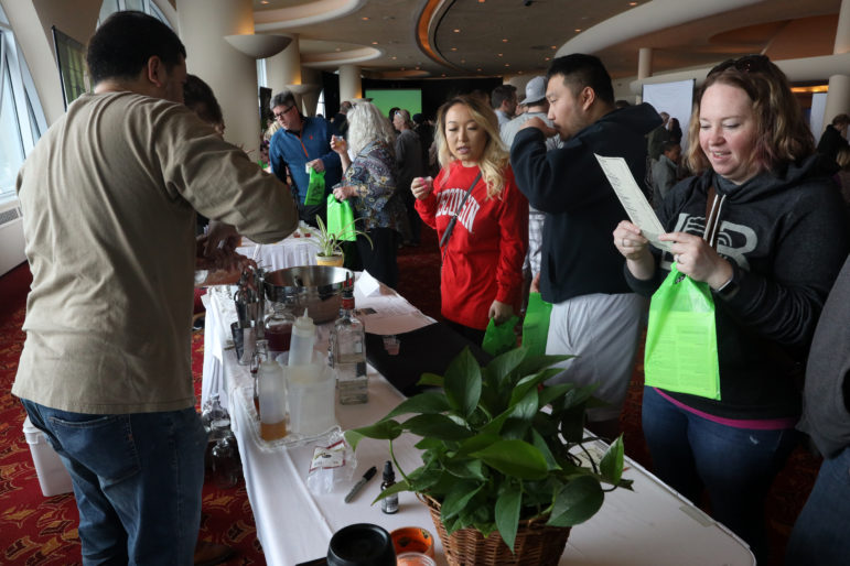 "People sample CBD cocktails at the Sweet Home Wisconsin Pub booth at the ""It's Hemp, It's Fine"" hemp/CBD event at Monona Terrace Convention Center in Madison, Wis., on April 7. The event featured a panel discussion, informational booths, and free samples of CBD coffee, beer, kombucha, candy and more. Photo by Coburn Dukehart / Wisconsin Center for Investigative Journalism."