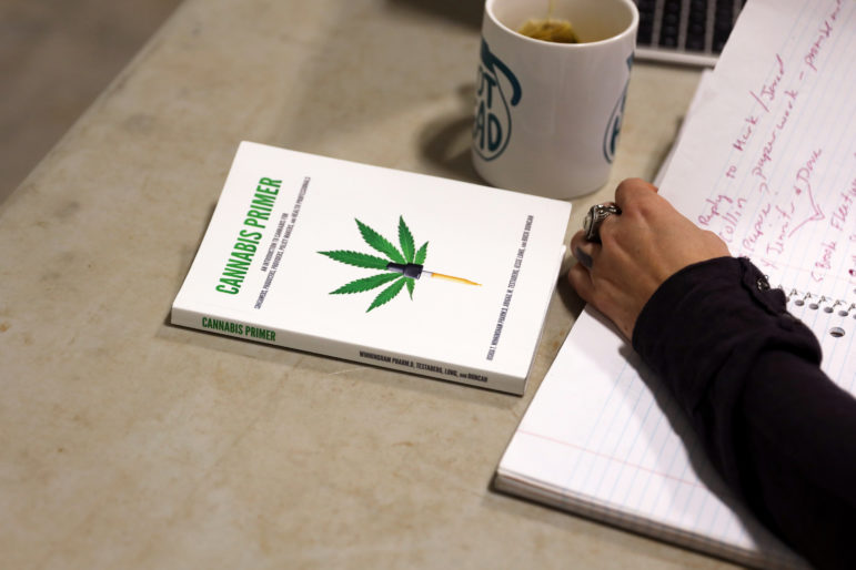 "The book Abbie Testaberg co-authored, ""Cannabis Primer"" is seen on the table as she and her husband Jody go through a to-do list at the Kinni Hemp Co., in River Falls, Wis., on April 18. Photo by Emily Hamer / Wisconsin Center for Investigative Journalism."