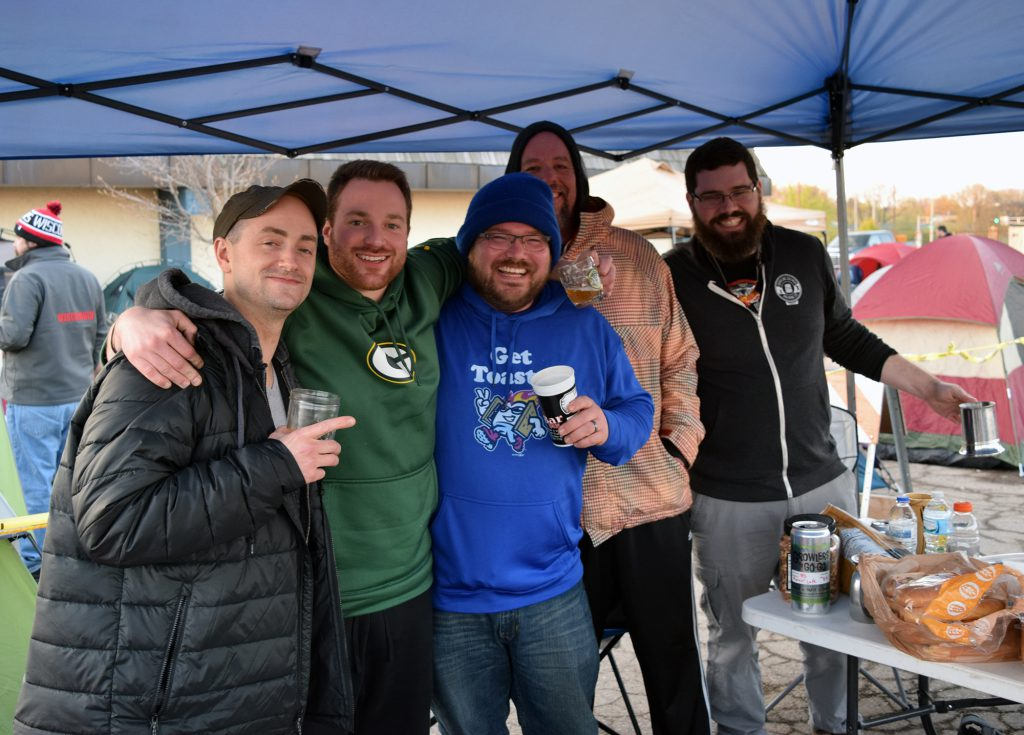 Zach Holder, left, Bill Disrud,center, Nick Courtney, right, and friends arrived before midnight on Sunday, May 5, 2019, to get in line to buy tickets for the Great Taste of the Midwest. Photo by Laurel White/WPR.