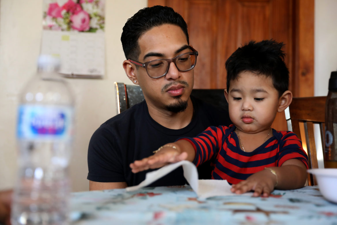 Erick Gamboa holds his son Adriel, 2, while the family has an afternoon snack in their Milwaukee home on Feb. 8, 2019. Gamboa, an undocumented immigrant from Mexico, was recently detained in the Kenosha County Detention Center for six months for illegally crossing the border in 2010, but a judge ruled he can stay in the United States. Unlike most immigrants, Gamboa had a lawyer to argue his case. Statistics show immigrants have a much lower chance of deportation if they have a lawyer. Photo by Coburn Dukehart/Wisconsin Center for Investigative Journalism.