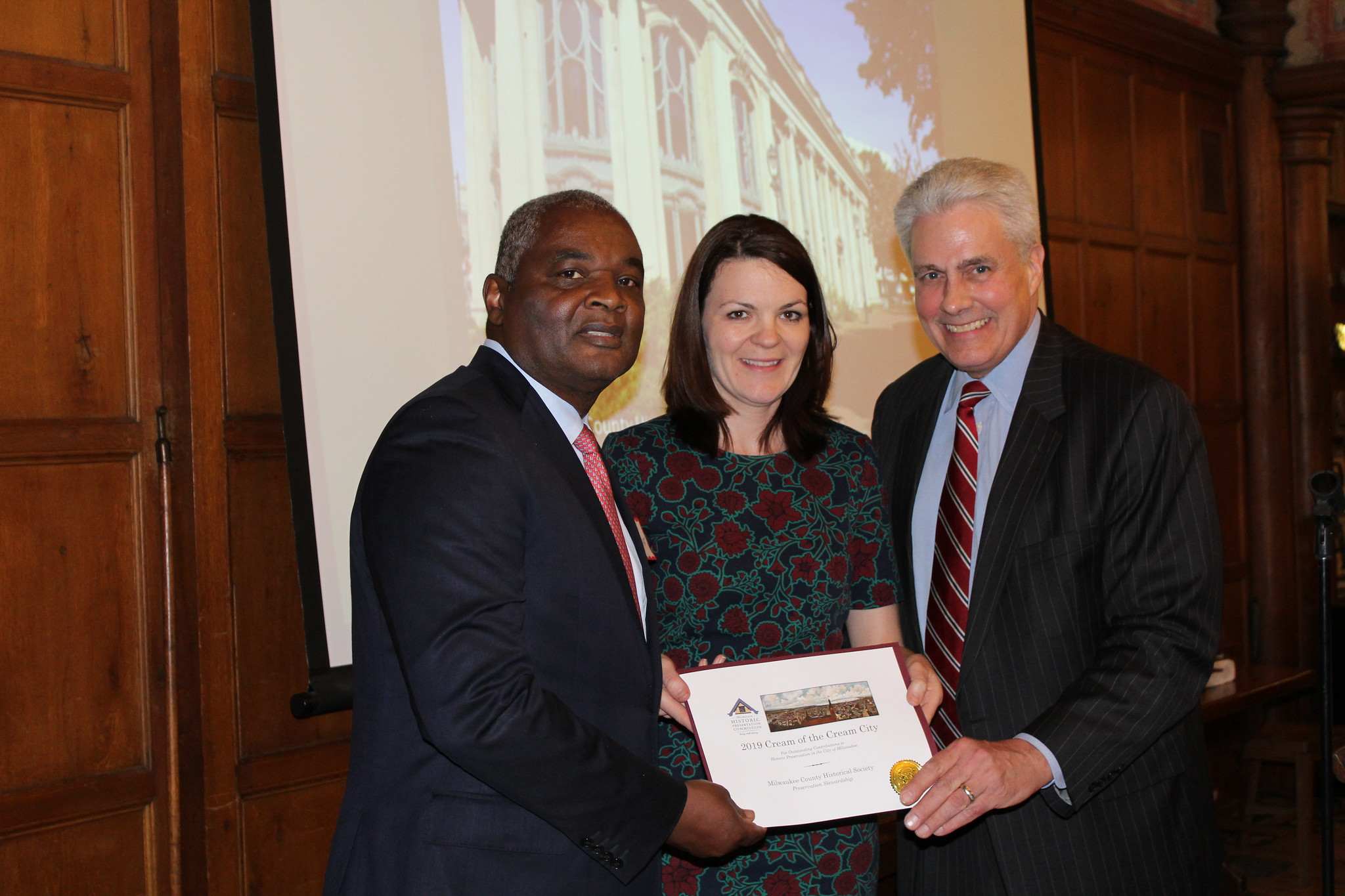 Alderman Robert Bauman (right) presents an award to Milwaukee County Historical Society past board chair Randy Bryant and executive director Mame McCully. Photo from the City of Milwaukee.