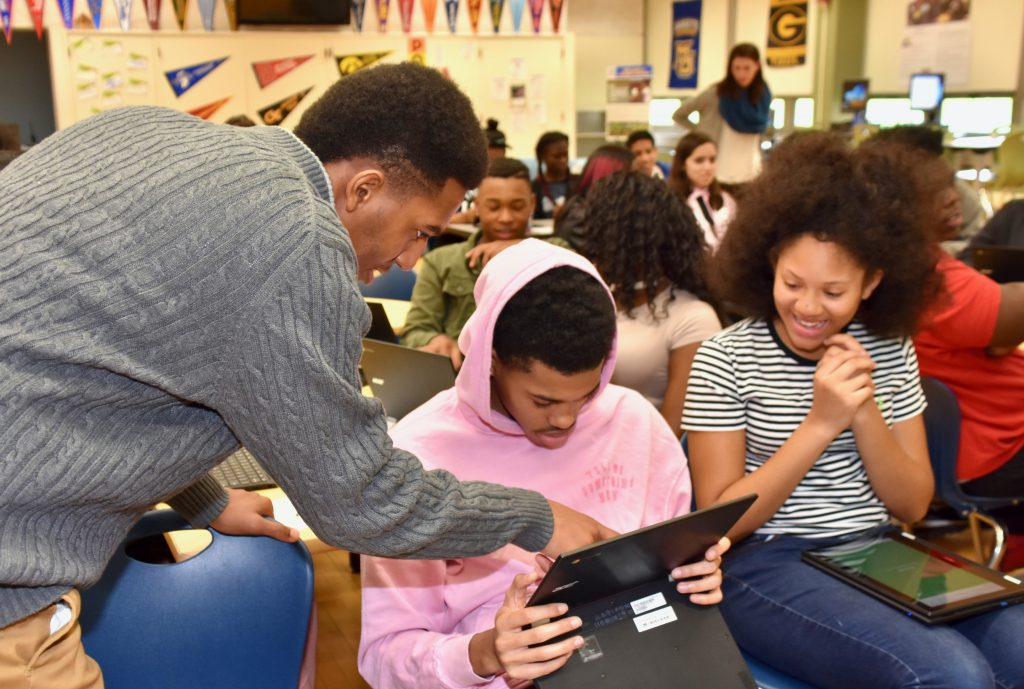 Tre'Quan Martin (left), planning assistant at Barack Obama School of Career and Technology Education's College and Career Center, helps students during a workshop. Photo by Patricia Kline/NNS.
