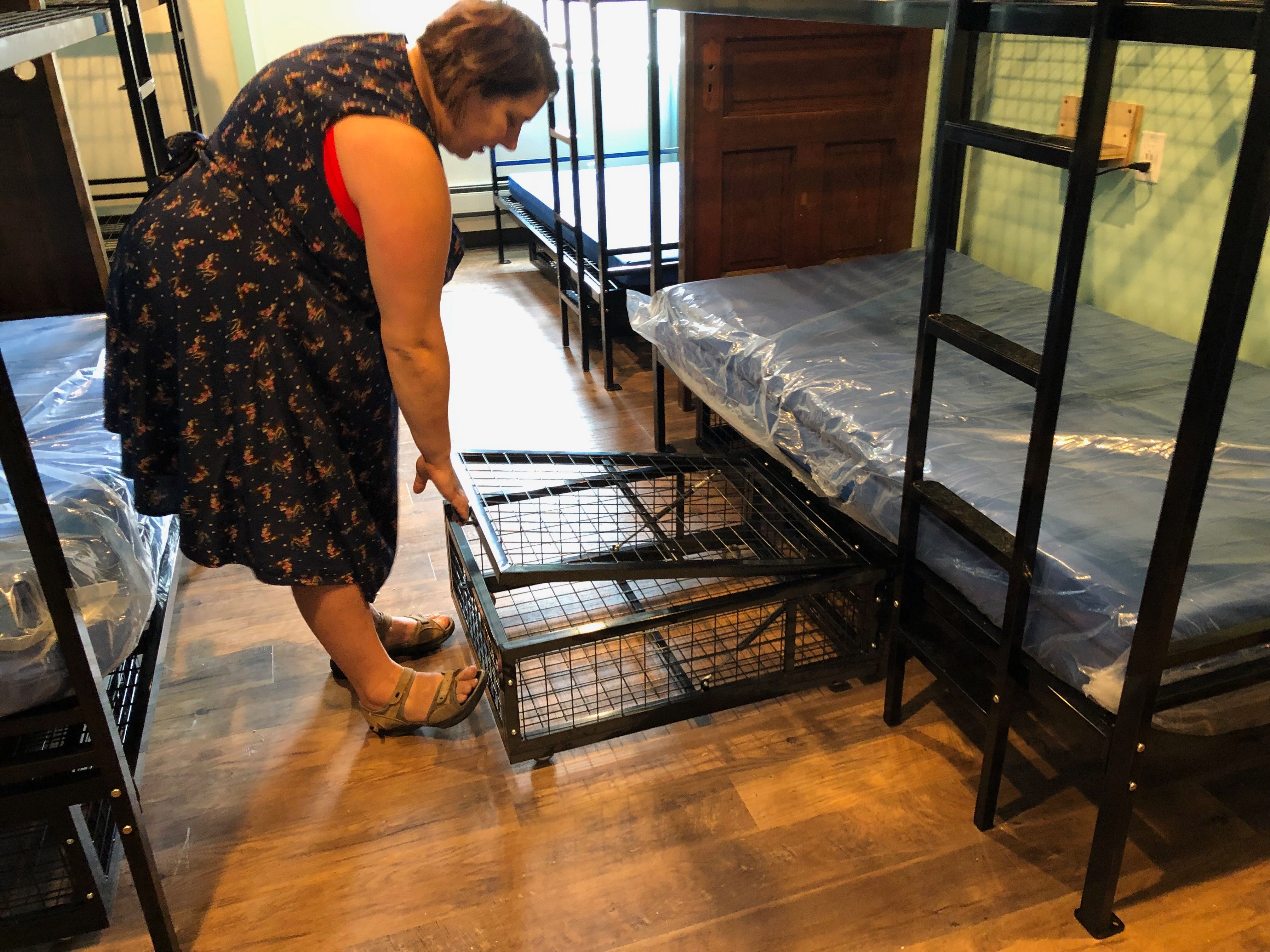 Wendy Mesich demonstrates one of the rolling lockers under bunk beds. The partners are working to complete the rooms in time for a late June opening. Photo by Jeramey Jannene.
