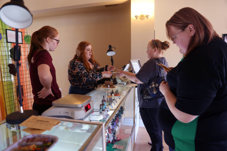 "Tera Jerrett, 34, buys a glass pipe from Isis Murphy-Kehoe, 20, at Kickapoo Kind, a CBD and hemp shop in Viroqua, Wis., on April 19. Skky Marsden, 27, of Soldiers Grove, at right, looks at products on display as Jerrett, of Readstown, makes her purchase. At left, Serena Murphy-Kehoe, 18, looks on. As she left the shop, Jerrett said, ""I'll be back for sure."" Isis and Serena are daughters of Kickapoo Kind owners Tim Murphy and Noelle Kehoe. Photo by Emily Hamer / Wisconsin Watch."