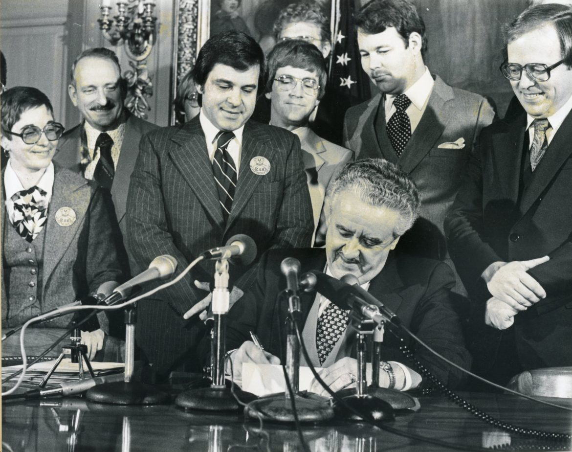 In 1979, Wisconsin Gov. Lee Sherman Dreyfus signed the bill that created the Citizen Utility Board. Others pictured include Lorraine Barniskis, policy director for House Majority Leader Jim Wahner; Rep. Wayne Wood; Rep. Wahner; Sen. Joe Strohl; Rep. John Norquist; Sen. David Berger; and Senate Majority Leader Bill Bablitch. Photo courtesy of the Wisconsin Citizens Utility Board.