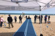 Unrolling a Mobi-Mat at Bradford Beach in Milwaukee June 3. Photo from The Ability Center.