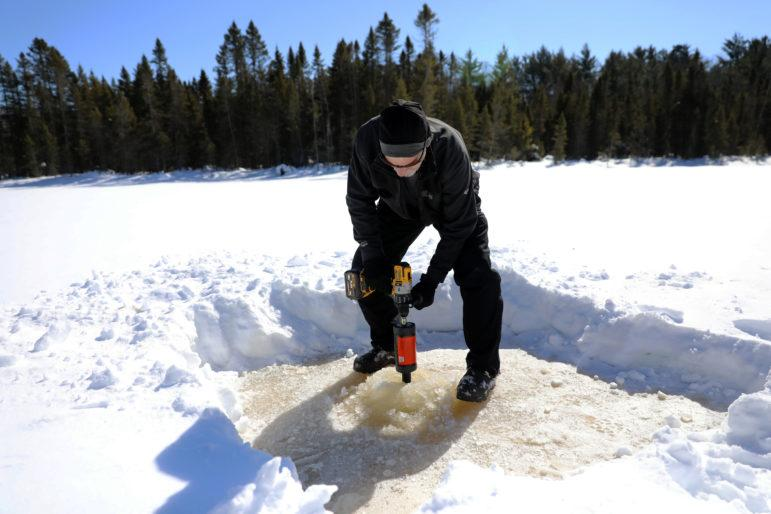 Jeff Rubsam uses a power auger to drill a hole in the ice of Little Rock Lake in Vilas County, Wis., on March 12, 2019. He is a research assistant for the state Department of Natural Resources and University of Wisconsin-Madison's Center for Limnology working with scientist Carl Watras to measure the levels of mercury in the lake over time. Photo by Sarah Whites-Koditschek/WPR.