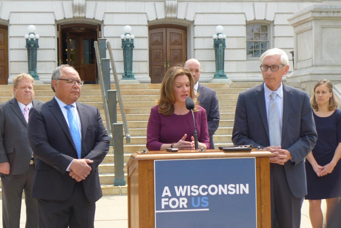 Department of Health Services Secretary Andrea Palm, joined by Commissioner of Insurance Mark Afable, left, and Gov. Tony Evers, right, speaks about expanding health coverage for Wisconsinites on Monday, June 3, 2019 in Madison. Photo by Shamane Mills/WPR.
