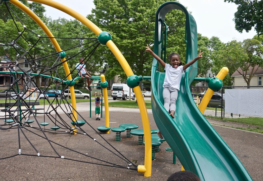 Denaja Shackelford, 5, lets loose on the slide at the Clarke Square playground, which was renovated by the county in 2013. Photo by Andrea Waxman/NNS.
