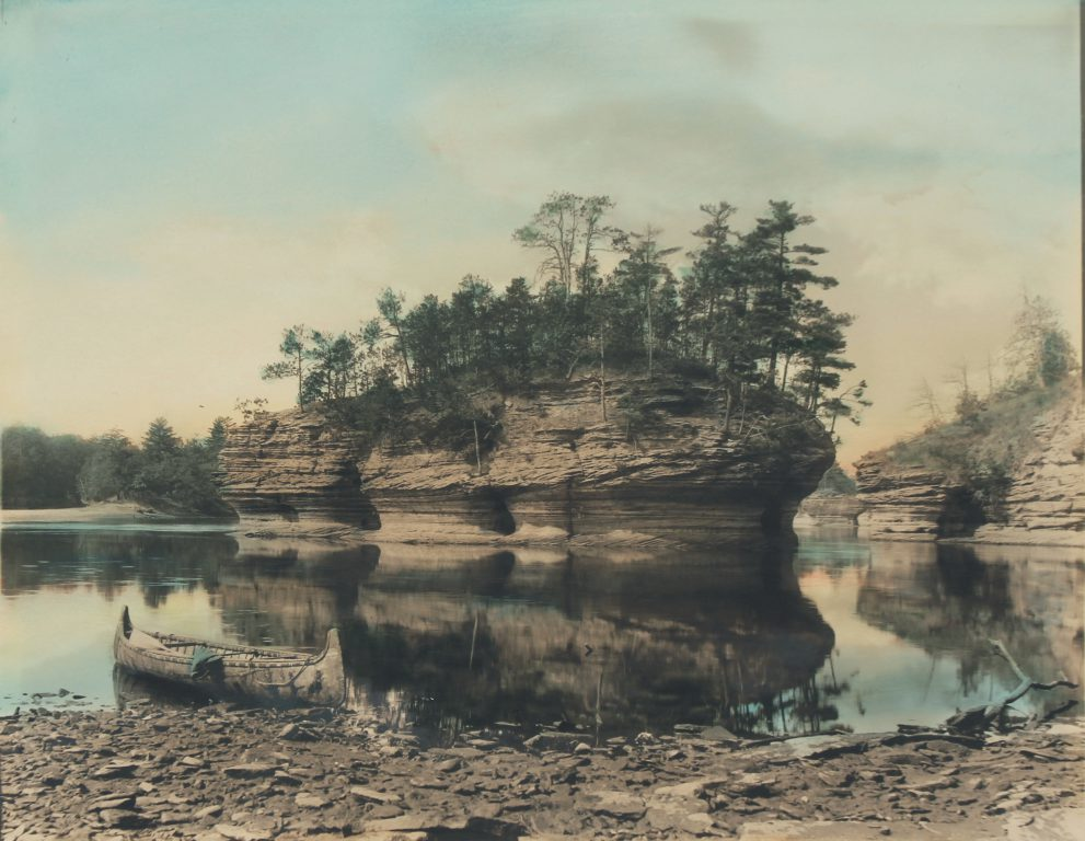 H. H. Bennett: Lone Rock with Canoe, ca. 1900. Albumen print with hand-tinting; 8 x 10 in., Museum of Wisconsin Art, 2004.006