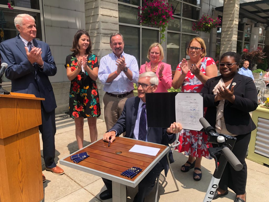 Governor Tony Evers shows the signed scooter bill, flanked by Mayor Tom Barrett, Tourism Secretary Sara Meaney and Assembly Representatives Mike Kuglitsch, Cindi Duchow, Christine Sinicki and LaKeshia Myers. Photo by Jeramey Jannene.