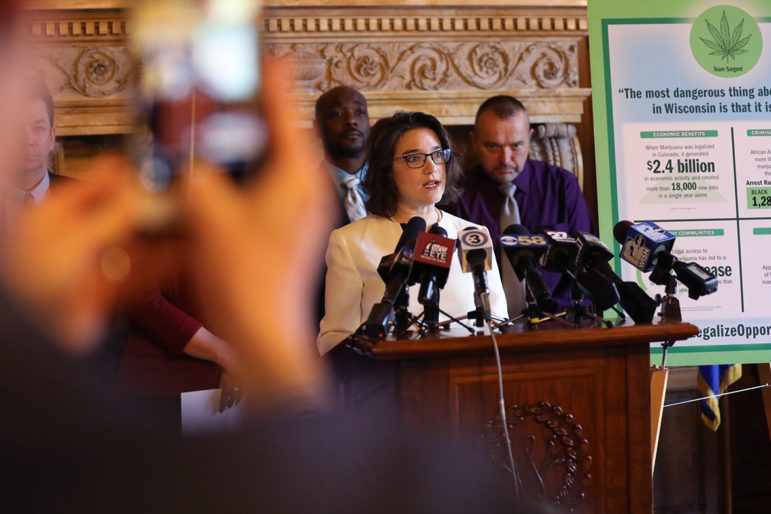 Rep. Melissa Sargent, D-Madison, announces she will introduce a bill to fully legalize marijuana in Wisconsin at the Wisconsin State Capitol in Madison, Wis., on April 18. She is flanked by, at left, Alan Robinson, executive director of the Wisconsin chapter of NORML; and Bob Daggett, a farmer from Montello, Wis. Sargent introduced the bill on May 17. Photo by Coburn Dukehart / Wisconsin Center for Investigative Journalism.