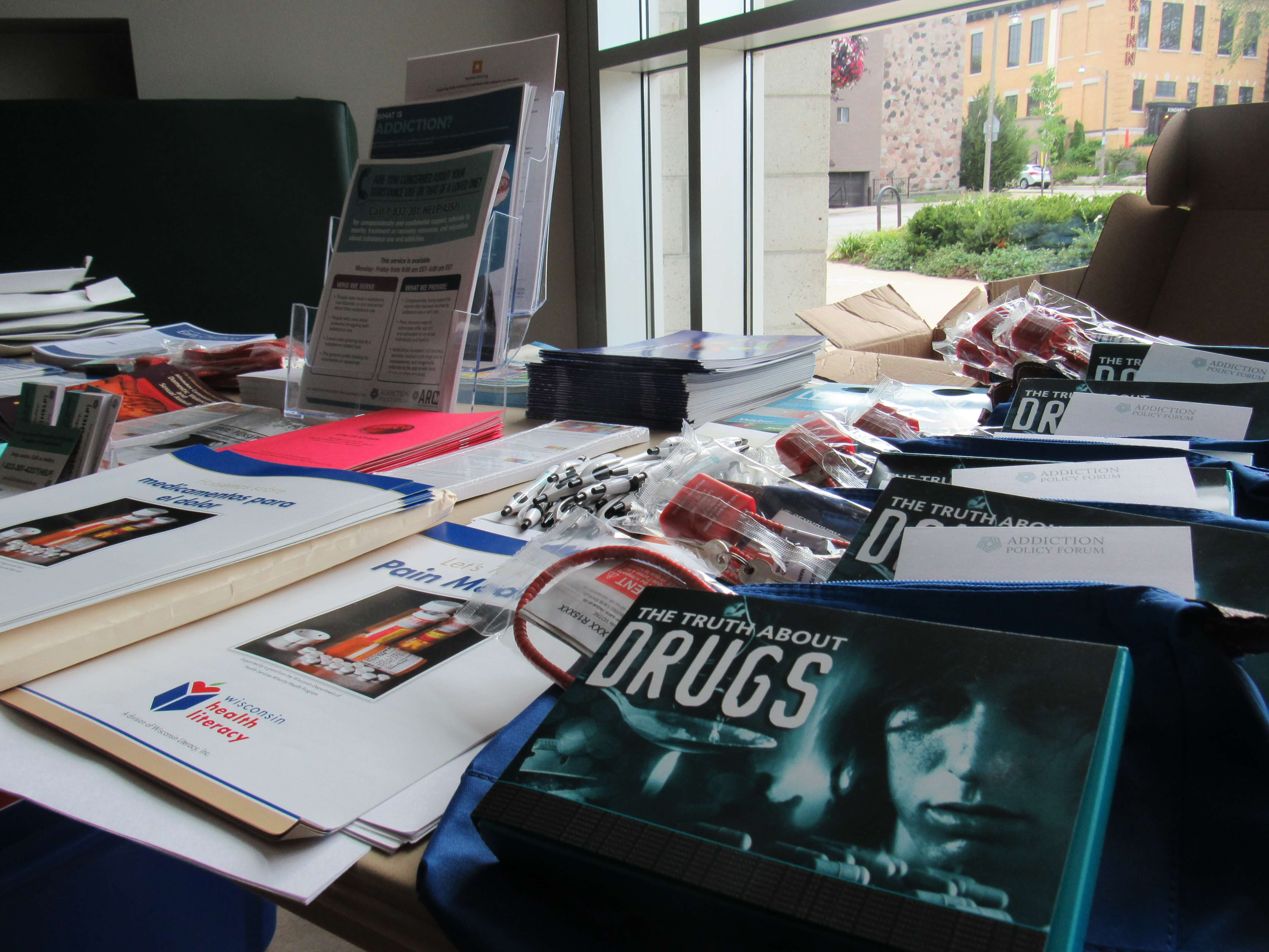 A table filled with information available at the Bay View library for the recovery event. Photo by Isiah Holmes/Wisconsin Examiner.