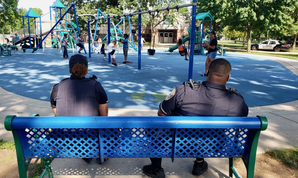 """Officers from Milwaukee Police Department's District 7 sit at a bench last week in Sherman Park. Willie Murphy, District 7 police captain, told NNS in a 2018 interview that """"I want to keep officers in their assigned areas, so the residents and officers can become familiar with each other and the problems that go on in the community."""" Photo by Edgar Mendez/NNS."""