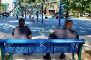 "Officers from Milwaukee Police Department's District 7 sit at a bench last week in Sherman Park. Willie Murphy, District 7 police captain, told NNS in a 2018 interview that ""I want to keep officers in their assigned areas, so the residents and officers can become familiar with each other and the problems that go on in the community."" Photo by Edgar Mendez/NNS."