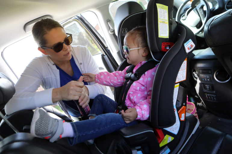 Lisa Kum puts her daughter, Emma, 2, into her carseat after playing in a park near Madison, Wis. Kum's husband Sothy Kum, a refugee from Cambodia, was deported in 2018 for a marijuana-related conviction. Immigration attorneys warn that immigrants should avoid using marijuana or investing in marijuana-related businesses — even in states where it is legal — because it remains illegal on the federal level. Photo by Coburn Dukehart / Wisconsin Watch.