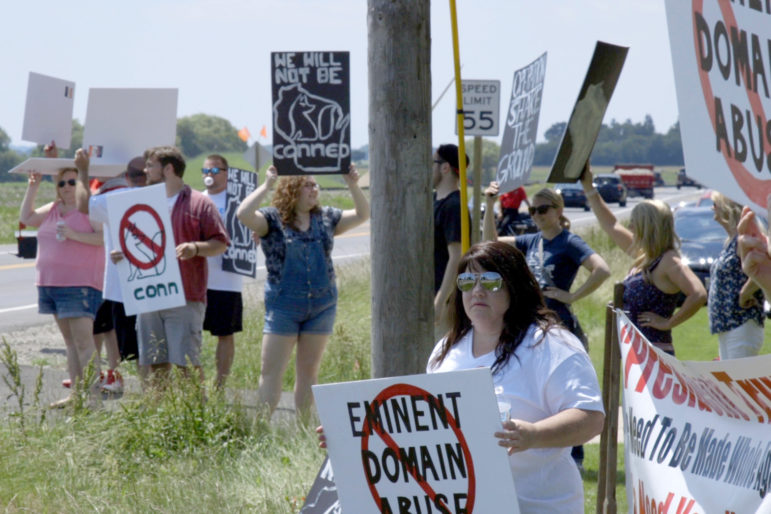 Kim Mahoney and other demonstrators gather at the corner of Braun Road and 105th Street in Sturtevant, Wis., on June 28, 2018, to protest the groundbreaking for the Foxconn manufacturing plant attended by President Donald Trump, then-Gov. Scott Walker, then-U.S. House Speaker Paul Ryan, and then-Foxconn chairman Terry Gou. Photo courtesy of Wisconsin Watch.