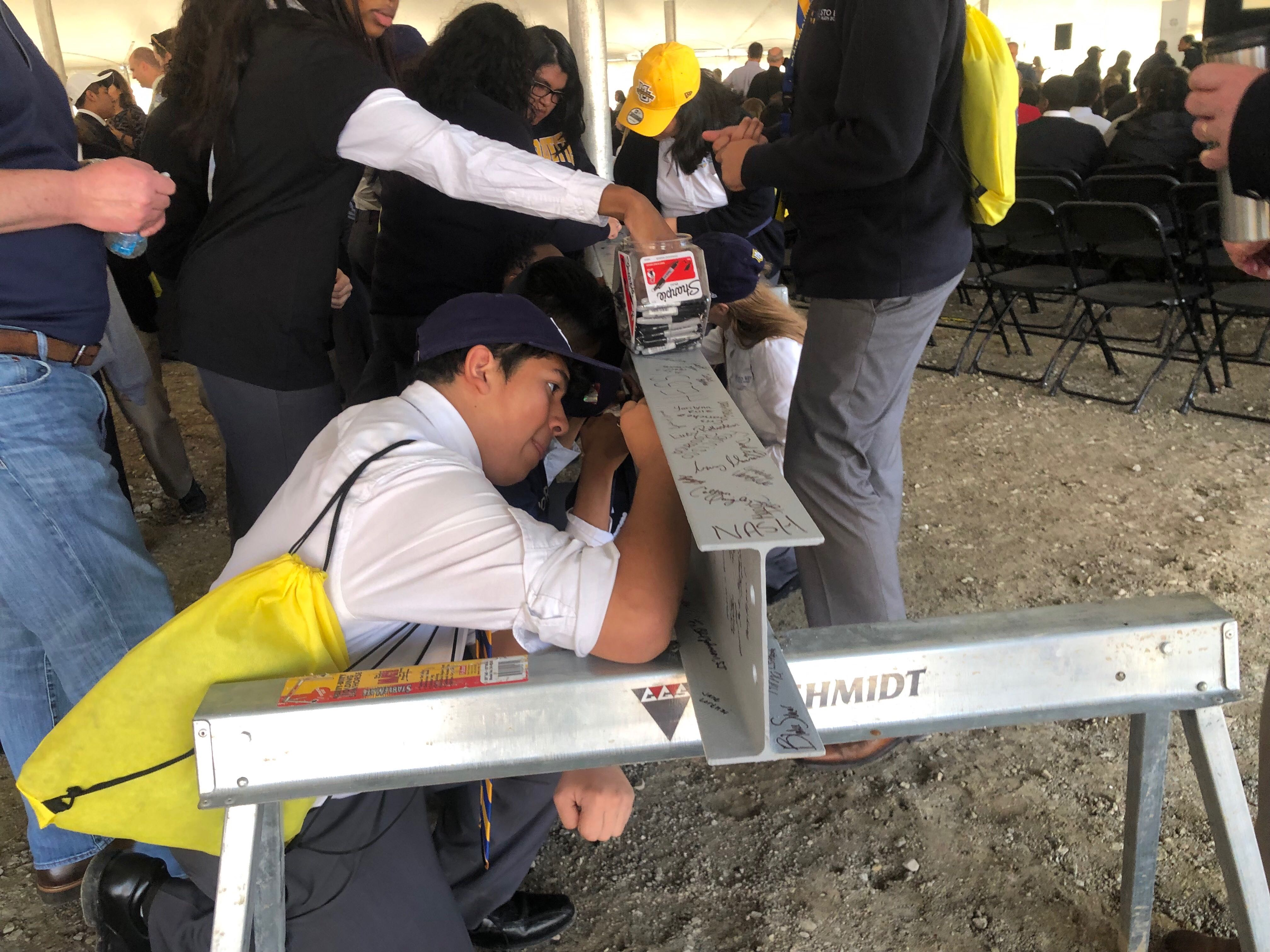 Cristo Rey students sign a steel beam to be used in the new school. Photo by Jeramey Jannene.